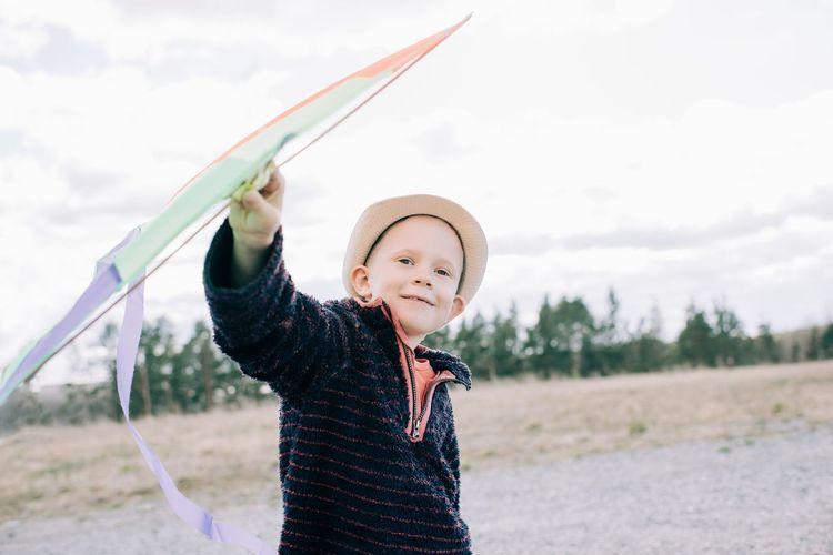 Portrait of boy standing on field against sky