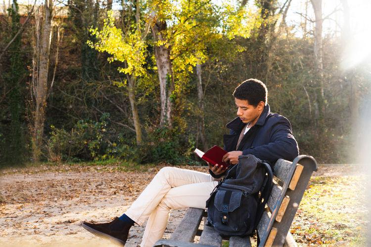 Full length of man reading book sitting at bench at park