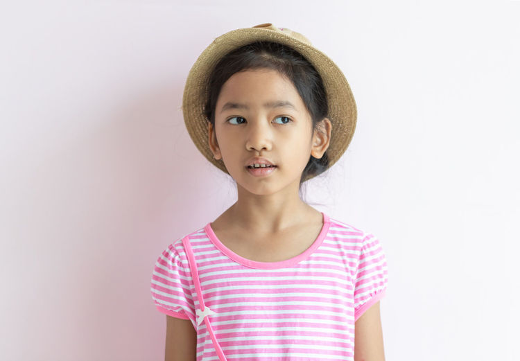 Portrait of girl standing against white background