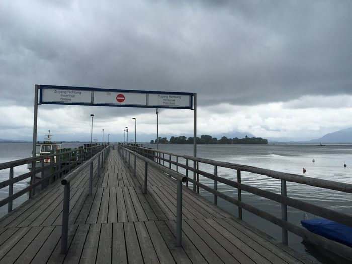 Cloud - Sky Sky Water Sea Nature Railing Pier Outdoors Direction Overcast Sign Day The Way Forward No People Transportation Communication Architecture Footpath