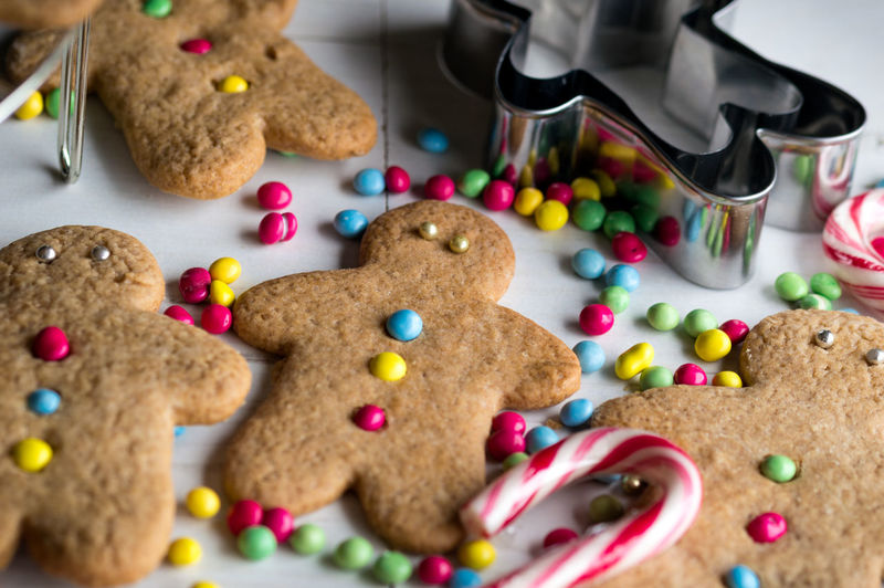 Close-up of gingerbread cookies with cutter and candy cane on table