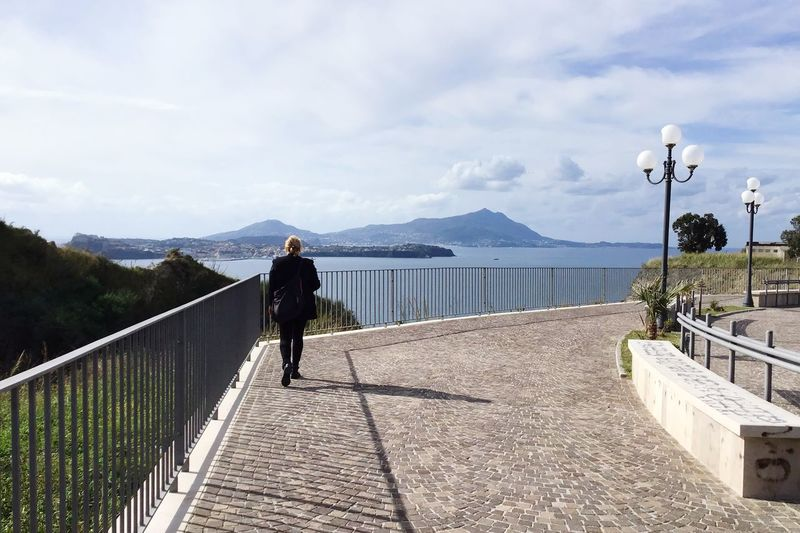 Rear view of woman walking on footpath by sea against sky
