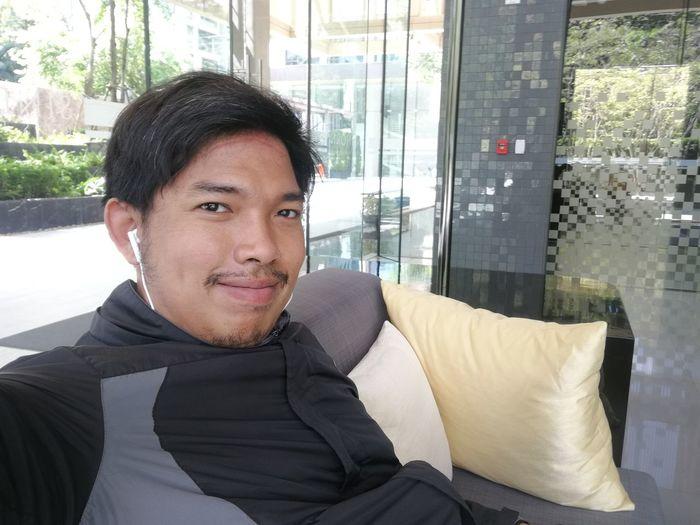 Portrait Of Smiling Mid Adult Man Sitting On Sofa Against Window