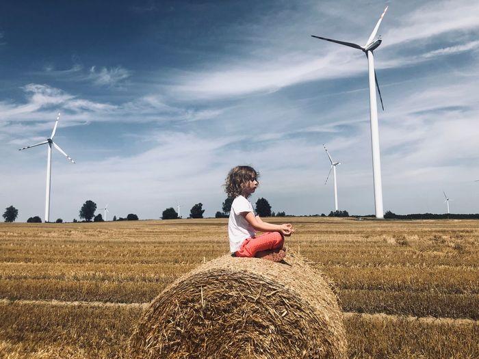 Girl meditating on hay bale