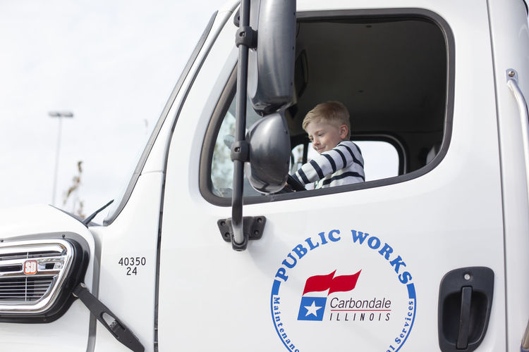 A five-year-old boy sits inside of a Carbondale Public Works truck and honks the horn during the touch-a-truck event at Saluki Stadium in October of 2018. Mode Of Transportation Transportation One Person Land Vehicle Men Headshot Real People Males  Car Motor Vehicle Portrait Sitting Driving Day Lifestyles Looking Communication Boys Truck Outdoors Innocence Trucking Boy Childhood Child