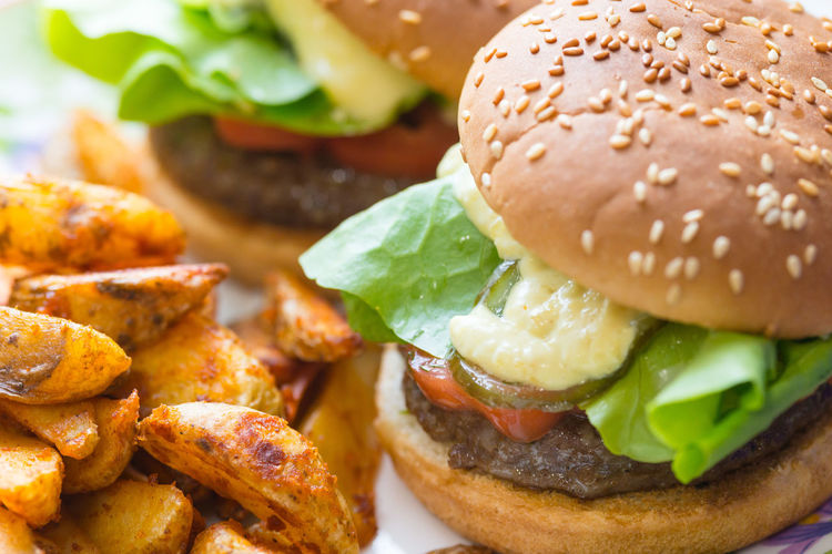 Close-Up Of Burgers And Fried Potatoes On Plate