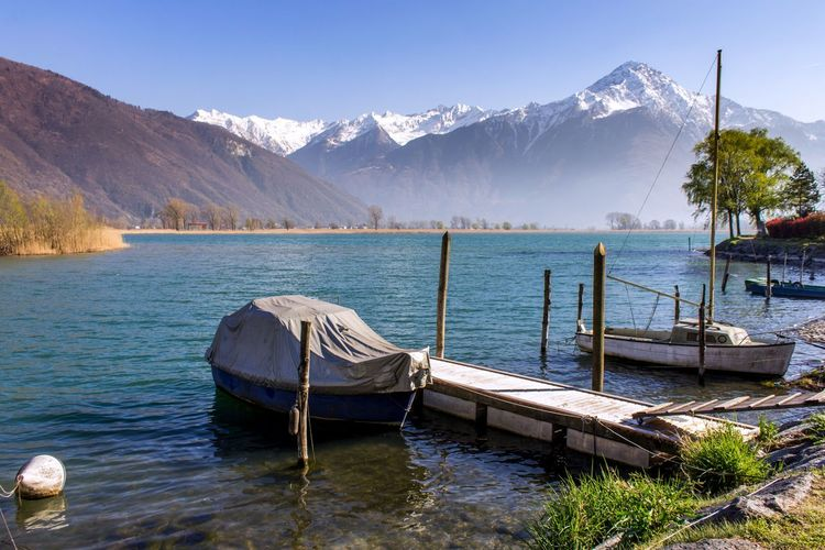 Boats Moored In Calm Lake Against Mountain Range