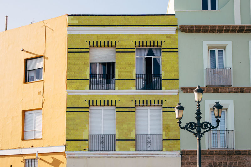 Yellow apartments in Seville, Spain Cadiz Colourful Houses Exterior Façade Holiday SPAIN Street Lamp Tourist Apartment Architecture Building Exterior Built Structure Day No People Outdoors Sky Summer Tourism Window Yellow Yellow Facade