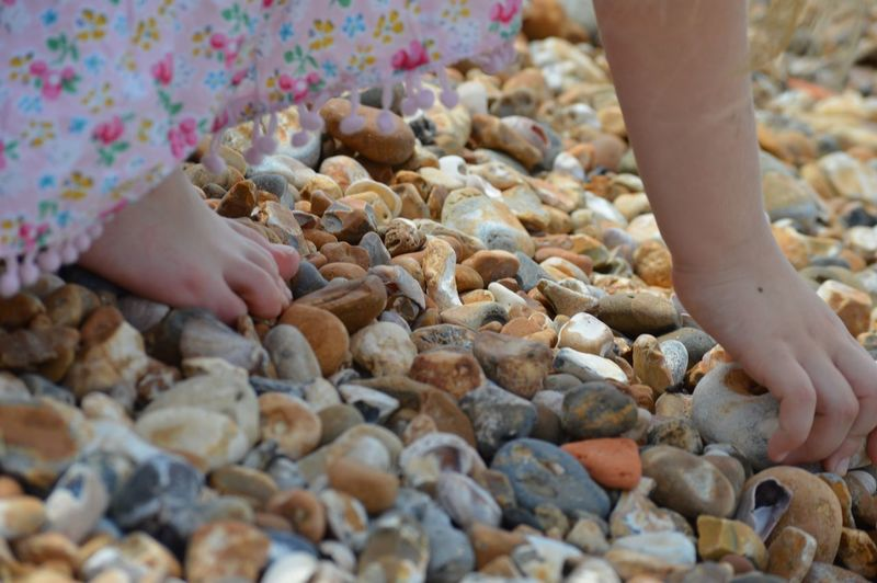 Low section of child on pebbles