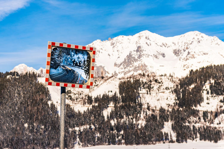 Winter road reflecting in a frozen mirror with snow-capped mountains in the background. schladming