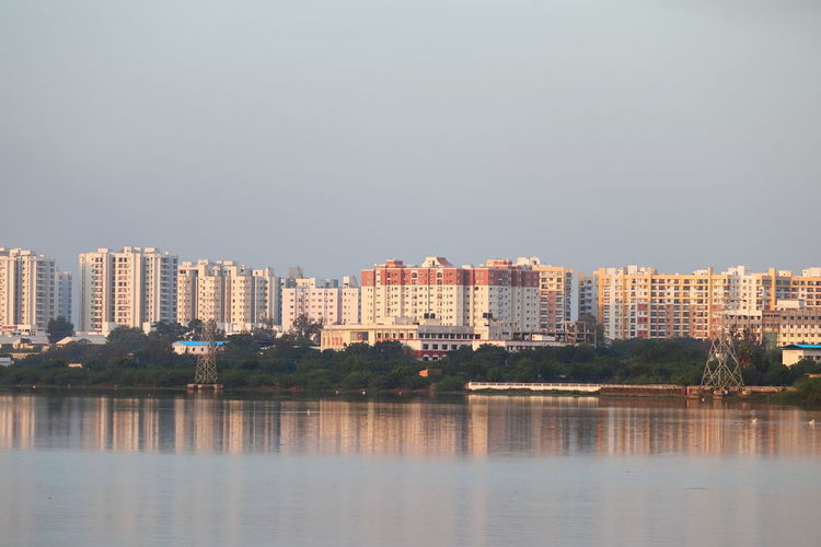 Buildings by lake against clear sky