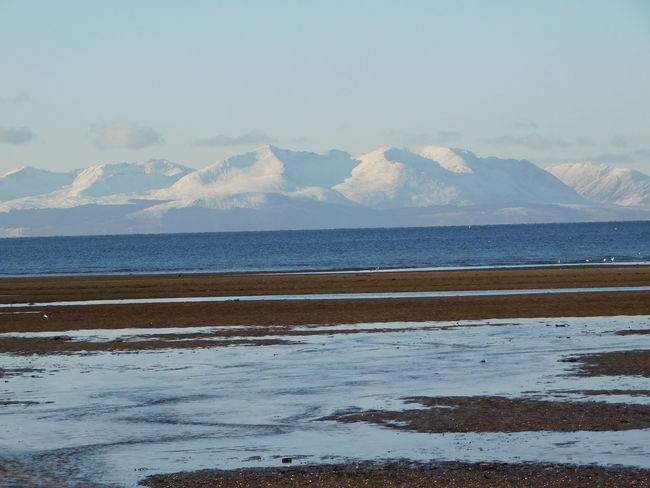 The beautiful snow capped hills of the Island of Arran as seen from the shoreline at Troon. Arran  Ayrshire, Scotland Coastline Winter Beach Beauty In Nature Beauty In Nature Blue Sky Horizon Over Water Island Landscape Mountain Nature No People Outdoors Sand Scenics Sea Shoreline Sky Snow Tranquil Scene Troon Water