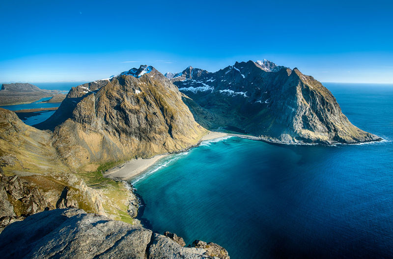 Kvalvika beach seen from high angle with mountains and ocean against blue sky in Lofoten, Norway Travel Destinations Lofoten Norway Mountains Beauty In Nature Ocean Sunny Day Water Sea Mountain Beach Blue Rock - Object Sky Landscape Travel