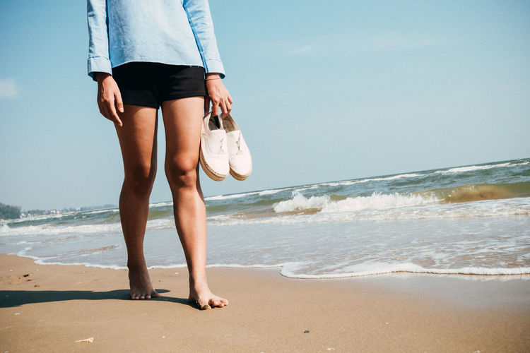 Beach travel - woman walking on sand beach Adult Beach Bikini Bottom Day Horizon Over Water Human Body Part Human Leg Lifestyles Low Section Motion Nature One Person Outdoors People Sand Sea Sky Summer Vacations Water Wave Women