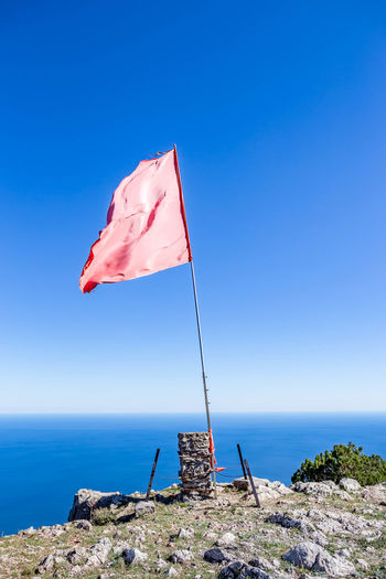 Sea Water Horizon Over Water Sky Scenics - Nature Blue Beauty In Nature Horizon Flag Nature Tranquility Day Tranquil Scene Rock No People Rock - Object Solid Idyllic Clear Sky Wind Outdoors