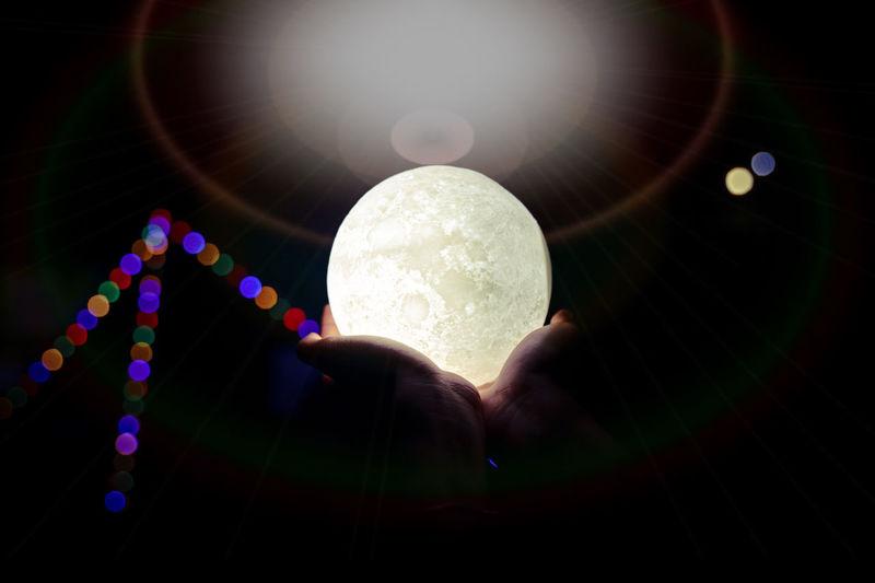 Digital composite image of hand holding illuminated light