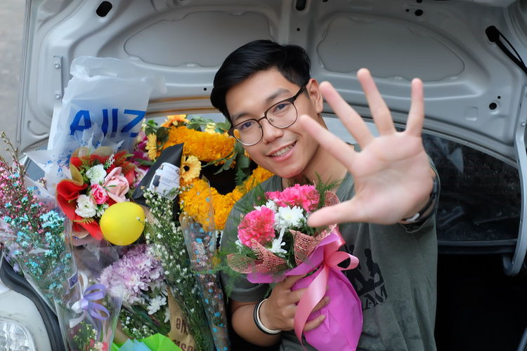 Portrait smiling of young man gesturing with bouquets in car trunk