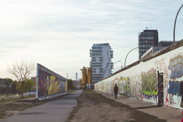 Architecture Built Structure Building Exterior City Sky Building Nature Footpath Day Outdoors Graffiti Street Direction Real People The Way Forward People Modern Cloud - Sky Art And Craft Plant Office Building Exterior Berlin Berlin Wall