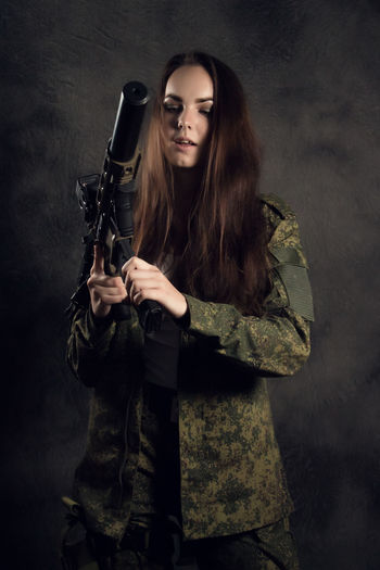 Adult Aggression  Aiming Beautiful Woman Brown Hair Clothing Government Gun Hair Hairstyle Handgun Holding Indoors  Long Hair One Person Portrait Sign Studio Shot Uniform Weapon Women Young Adult