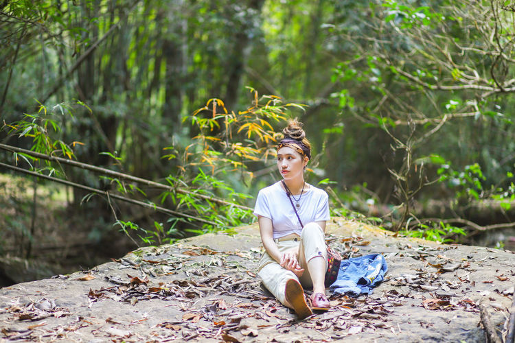 Thoughtful young woman sitting on rock against trees in forest