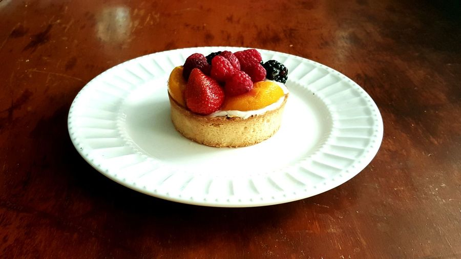 High Angle View Of Fruit Tart In Plate On Wooden Table