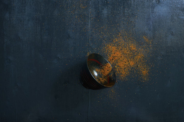 Directly above view of bowl with scattered spice on table