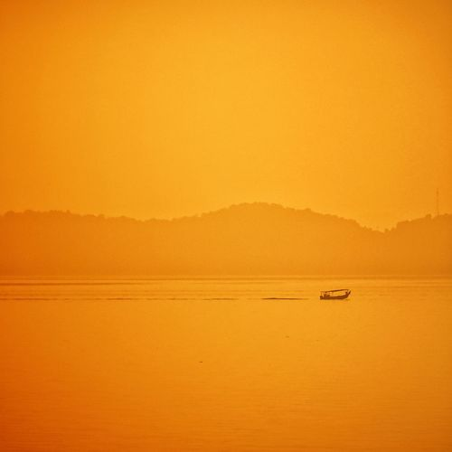 Scenic view of sea against orange sky