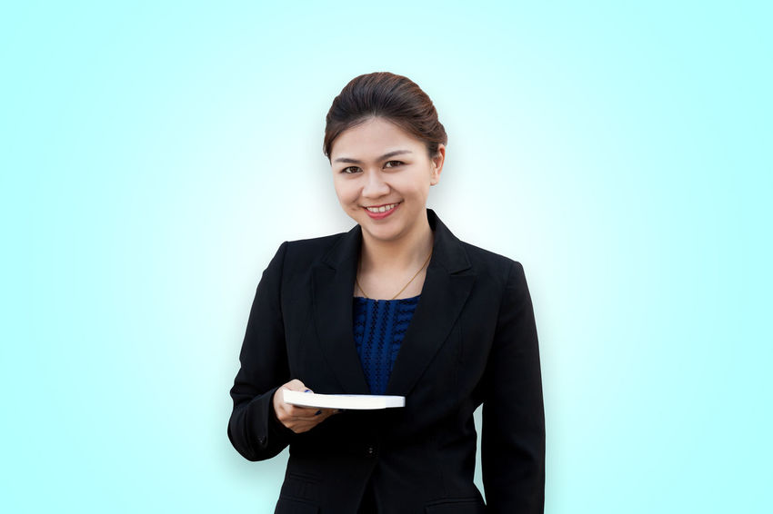 Asian businesswoman with book in hand Asian  Isolated Office Thai Book Business Businesswoman Colored Background Concept Copy Space Diary Education Give Giving Hand Holding Looking At Camera Notebook Paper Portrait Showing Smiling Studio Shot Suit Textbook