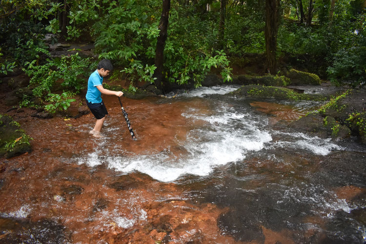 Boy standing in stream at forest