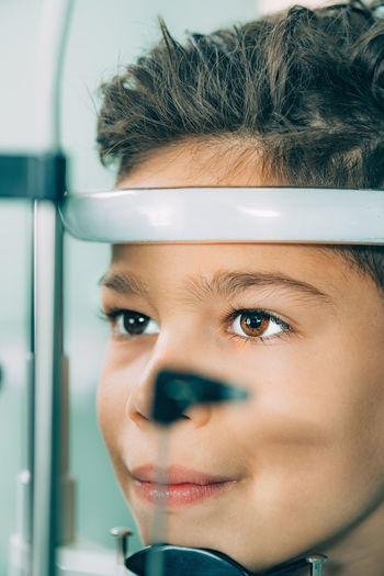 Close-up of boy with eye test equipment
