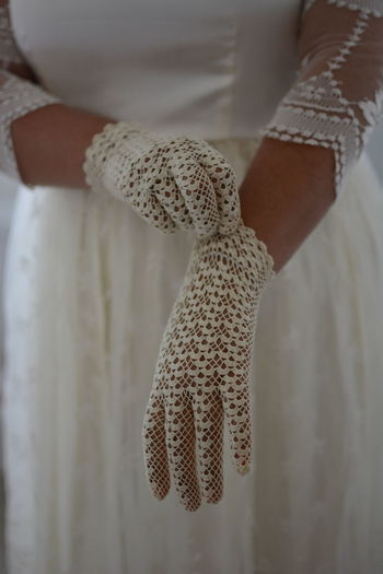 Midsection of bride adjusting gloves