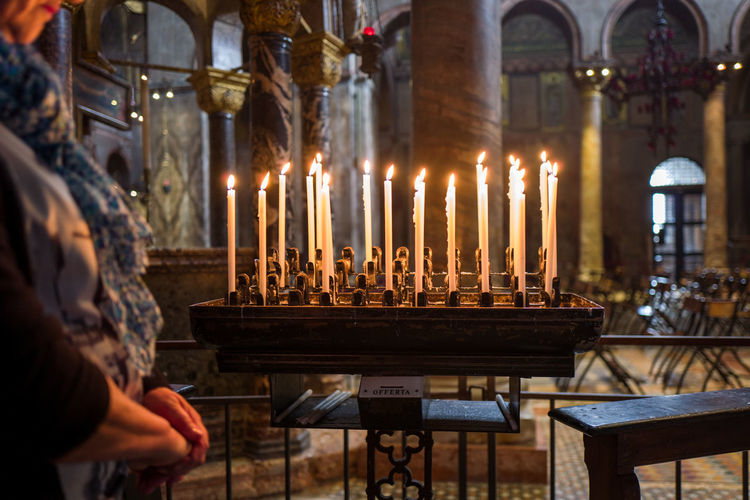 Midsection of woman standing by lit candles in church
