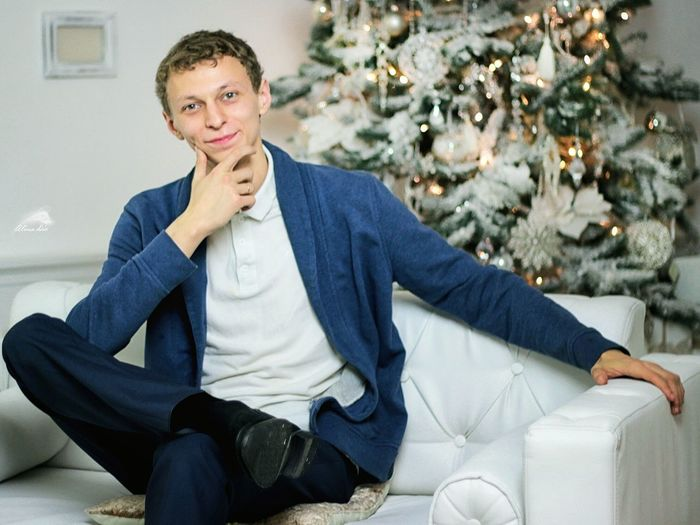 Portrait of man sitting with christmas tree