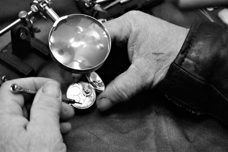 High angle view of cropped hands repairing pocket watch