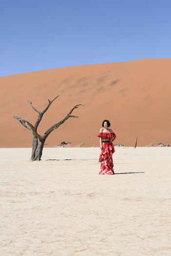 Woman standing on sand against clear blue sky