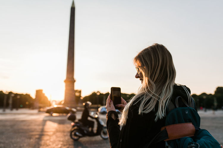Woman taking a picture with her mobile phone at place de la concorde in paris during sunset