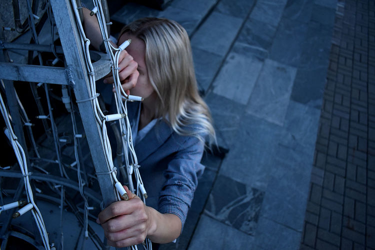 High angle view of woman crouching by gate outdoors