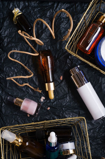 set of nature precious oils and care cosmetics on black background . High Angle View Indoors  No People Still Life Choice Large Group Of Objects Close-up Variation Table Directly Above Container Metal Body Care Flame Fire Brush Burning Collection Black Color Paintbrush