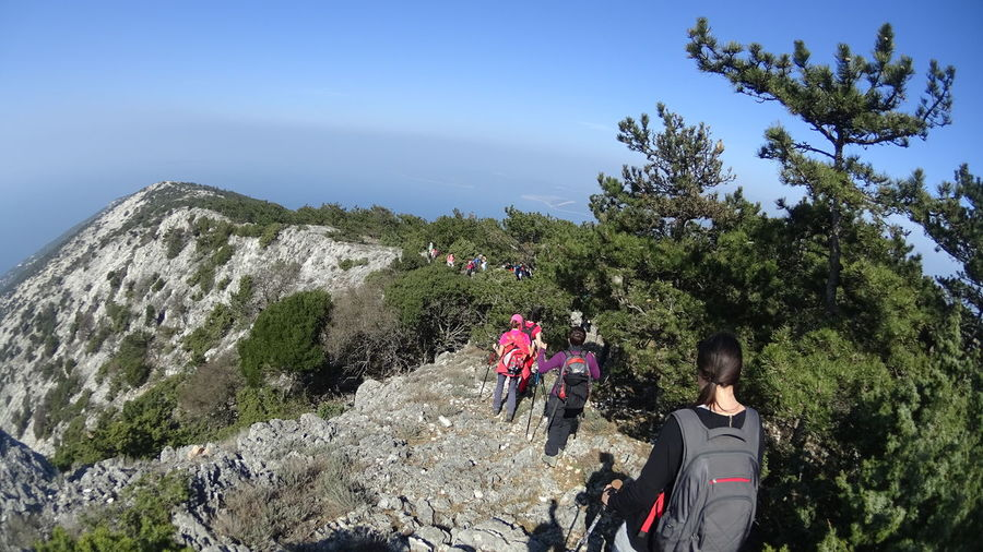 High angle view of hikers walking on mountain against clear sky