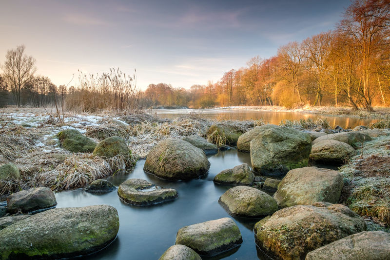 Rocks by river against sky during sunset