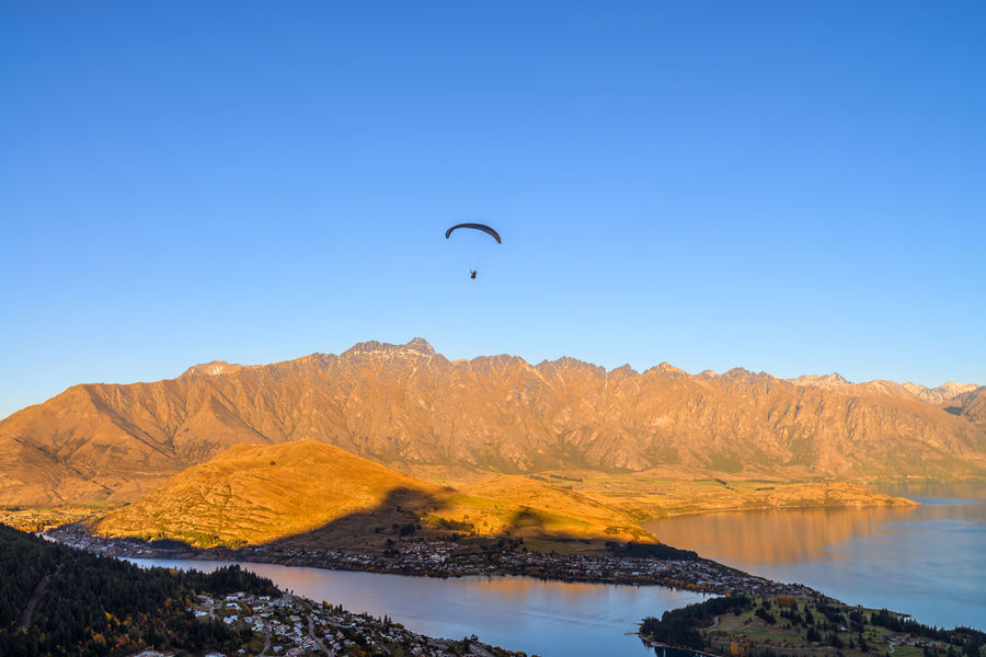 Paragliding during sunset at Queenstown from Ben Lomond Hill, overlooking the Queenstown, Lake Wakatipu and The Remarkable mountain range Beauty In Nature Blue Clear Sky Day Flying Hot Air Balloon Mountain Nature No People Outdoors Paragliding Scenics Sky Travel Destinations