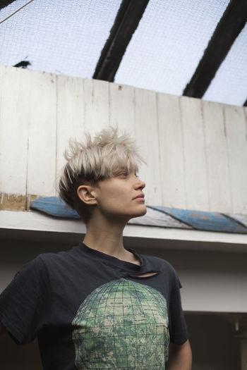 Portrait of teenage boy standing against built structure