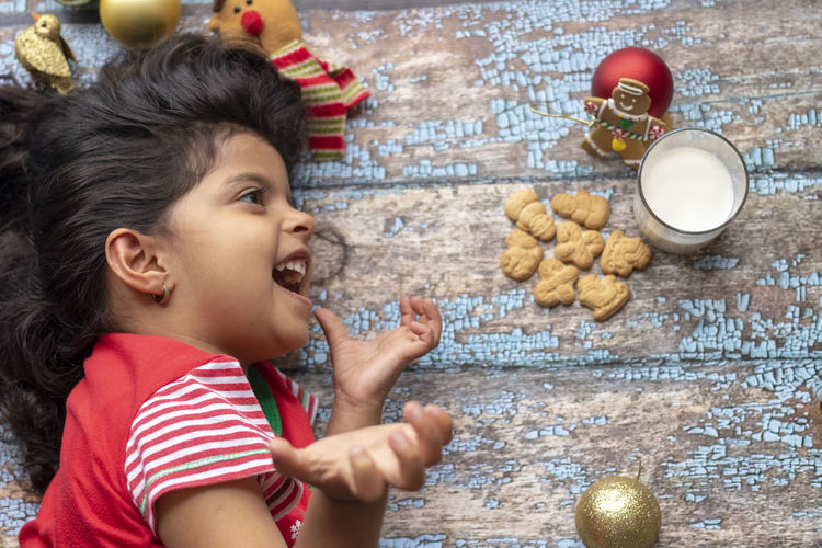 Cute little girl is playing with Santa's cookies and milk at Christmas Childhood Child Food And Drink Food One Person Lifestyles Indoors  Boys Holiday Christmas Happiness Cute Cookie Girls Real People Side View Portrait Celebration Innocence Mouth Open