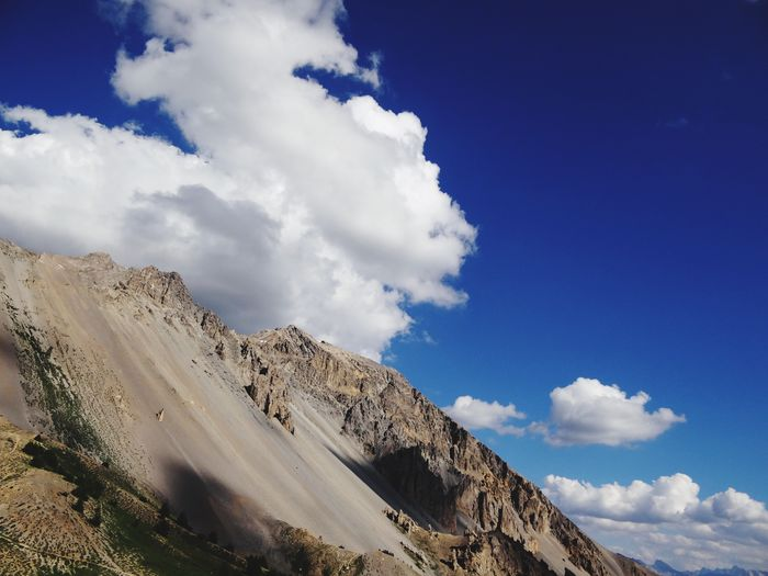Low angle view of rocky landscape against blue sky and clouds