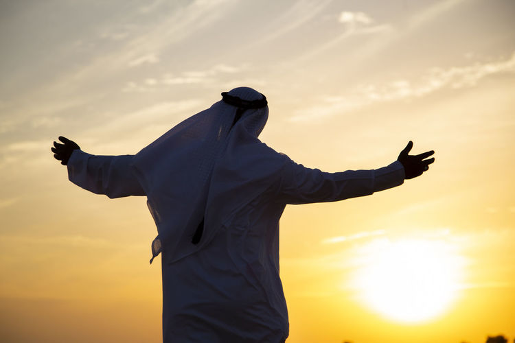 Rear view of man in traditional clothing standing against sky during sunset