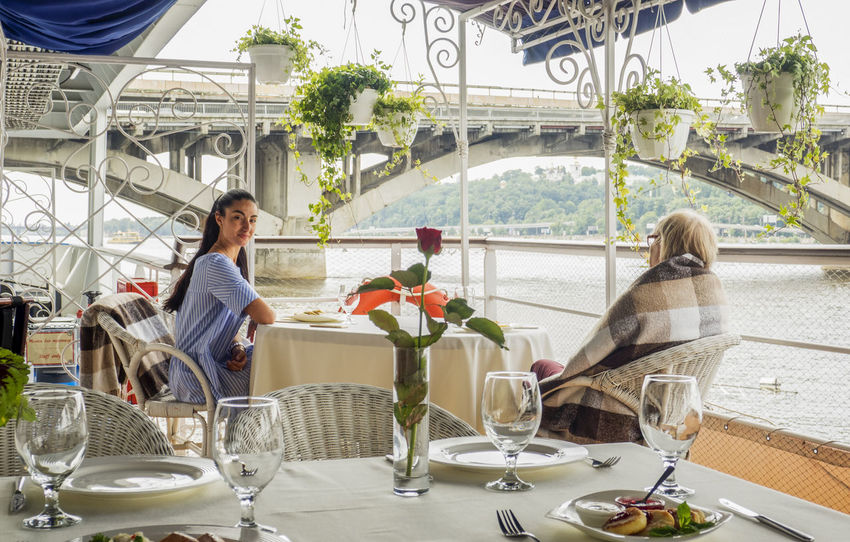Two woman seats at the table set for breakfast on the deck of a ship and looking for the water Breakfast Metro Woman Adult Adults Only Bridge Caucasian Chair Day Deck Dnieper Drink Flower Food And Drink Indoors  Leisure Activity Lifestyles Looking People Place Setting Plate Real People River Ship Sitting Subway Table Two Two People Water Wineglass Women Young Adult Young Women