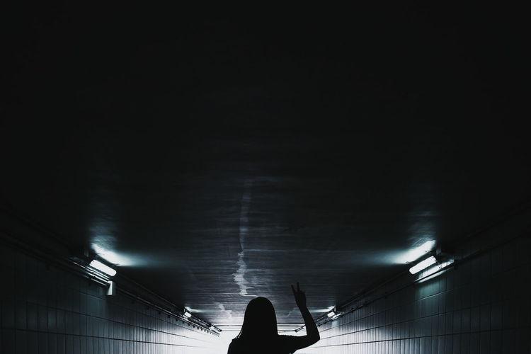 Woman in illuminated tunnel