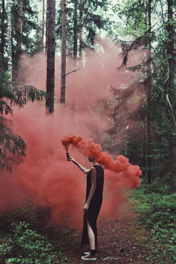 Woman Holding Flare In Forest