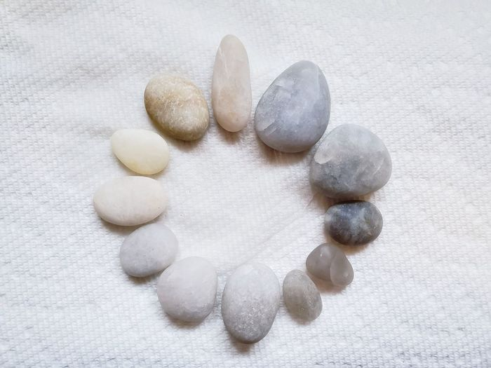 High angle view of pebbles on white surface