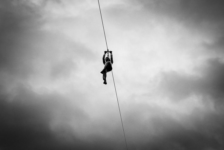 Low angle view of man hanging on rope against sky